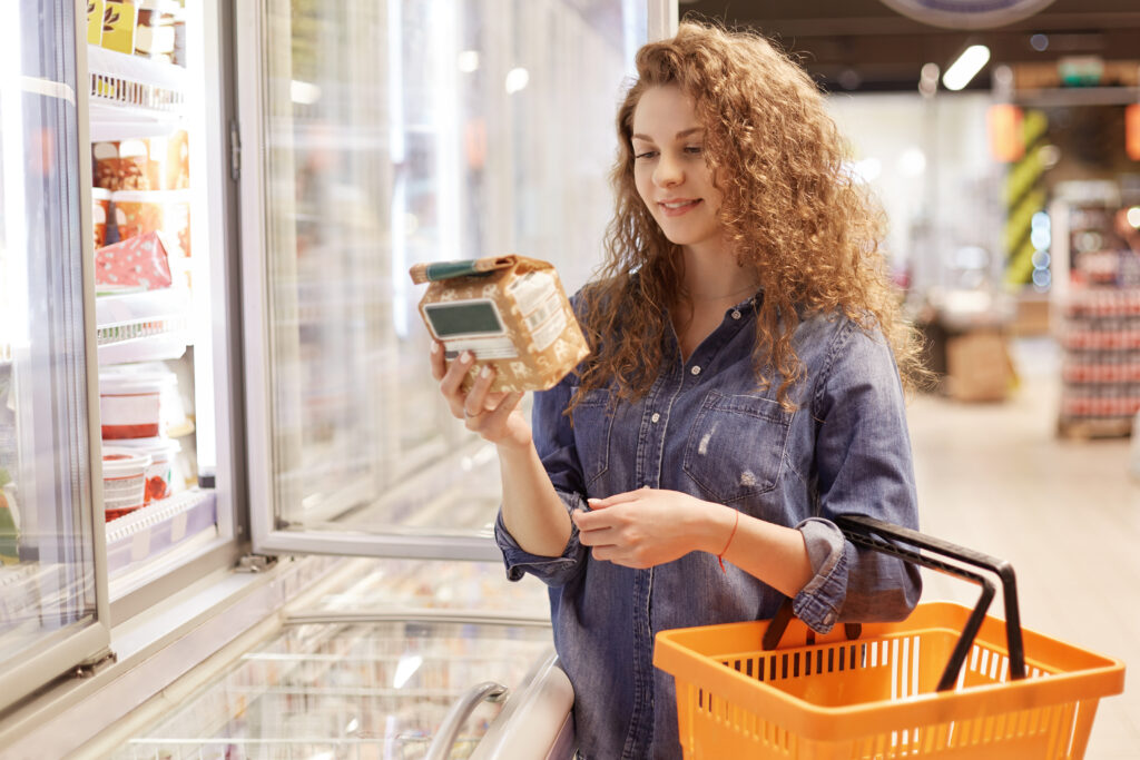 Woman reading food label while shopping