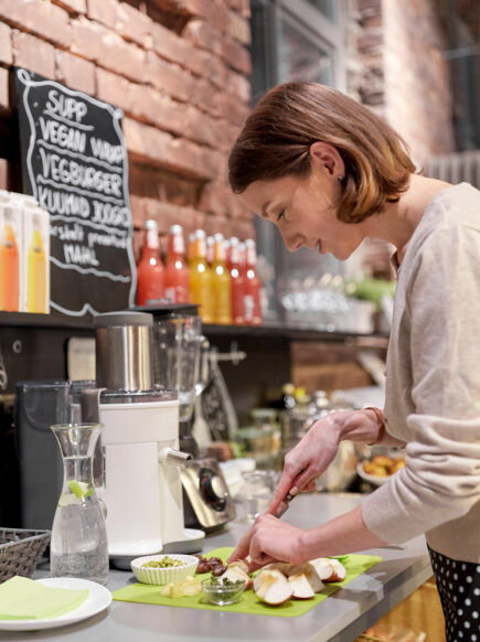 Woman prepares food at plant-based cafe